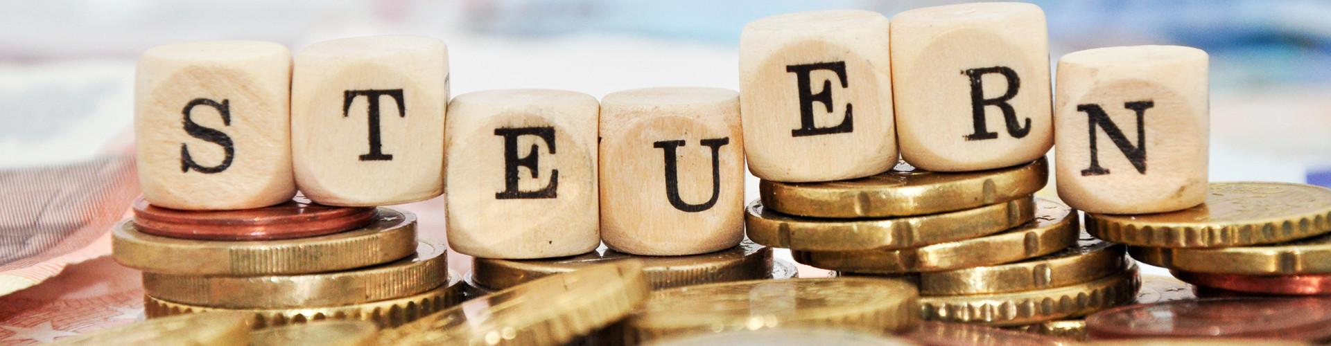 """Buchstabenwürfel, welche auf einem Stapel Euro-Münzen liegen, bilden das Wort """"Steuern"""" © Marco2811, stock.adobe.com"""
