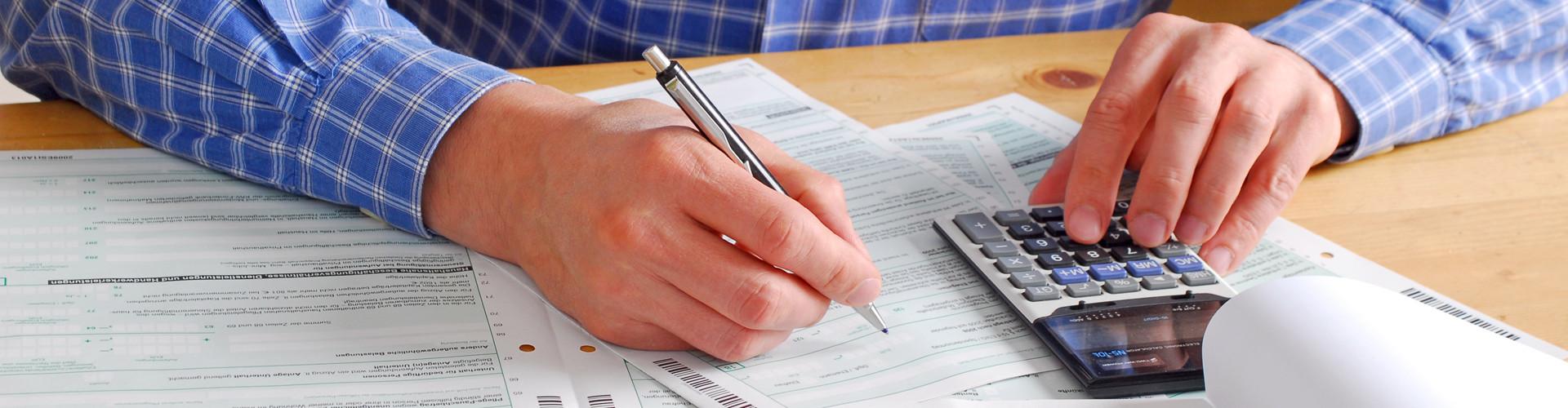Man sieht die Hände eines Mannes, der sich über einen Tisch mit Formularen beugt. In der einen Hand hält er einen Stift, mit der anderen bedient er einen Taschenrechner. © photophonie, stock.adobe.com
