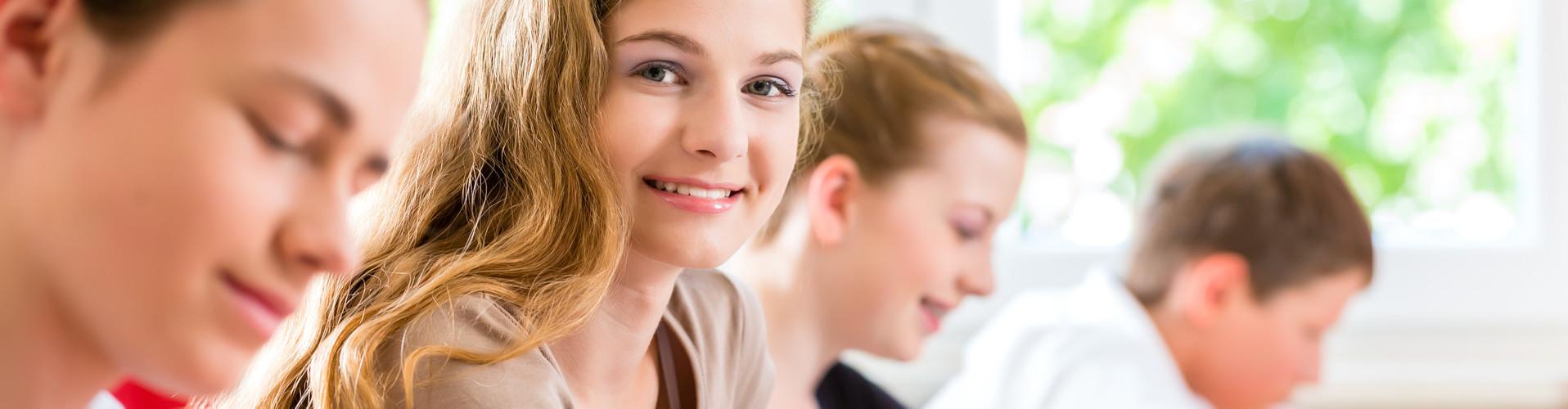 Zwei männliche und zwei weibliche Schüler sitzen im Klassenzimmer und schreiben, eines der Mädchen lächelt den Betrachter an © Kzenon, stock.adobe.com