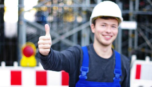 Junger Mann in Arbeitskleidung streckt Daumen in die Höhe © Wellnhofer Designs, stock.adobe.com
