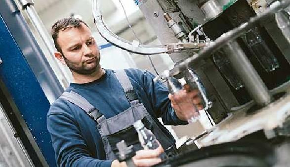 Arbeiter am Fließband kontrolliert Plastikflasche © duskojovic, Fotolia.com