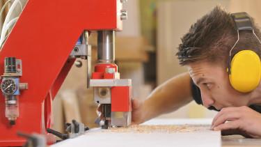 Ein männlicher Jugendlicher mit Gehörschutz steht an einer Werkbank und bearbeitet ein Holzbrett mit einer Fräsmaschine. © jörn buchheim, stock.adobe.com