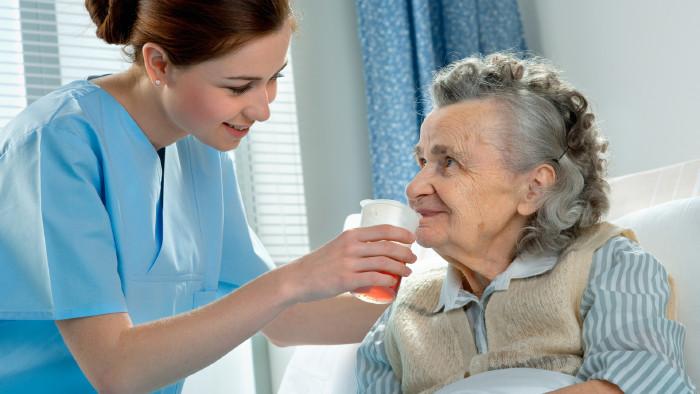 Pflegerin gibt älterer Dame zu trinken © Alexander Raths, stock.adobe.com
