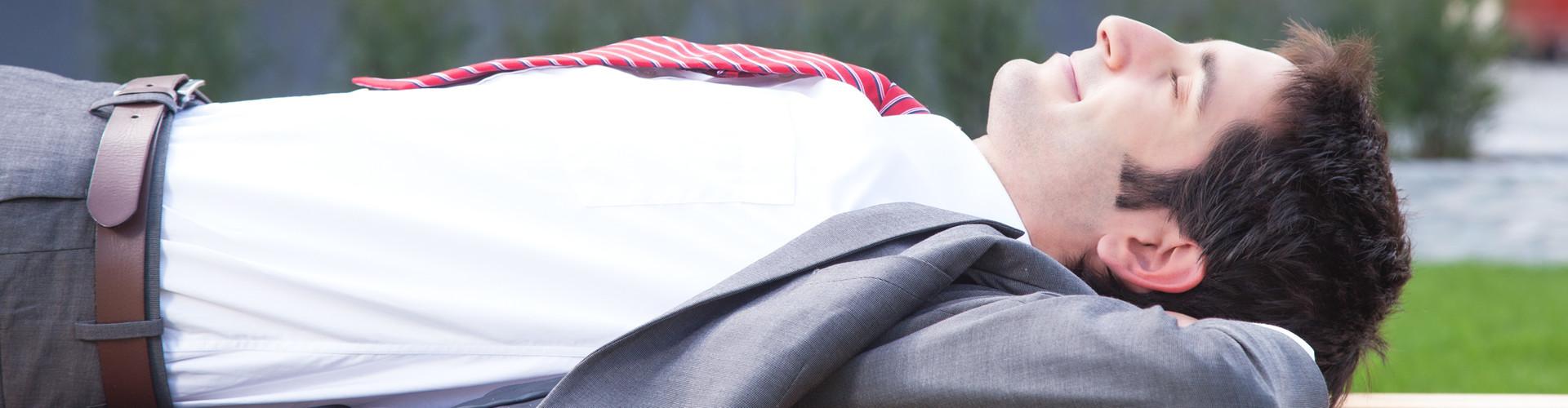 Ein Angestellter liegt auf dem Rücken in der Sonne und hat die Arme hinter dem Kopf verschränkt © Daniel Ernst, stock.adobe.com
