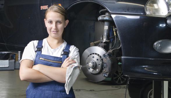 Automechanikerin steht stolz vor einem aufgebockten Fahrzeug © runzelkorn, stock.adobe.com