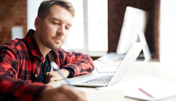 Junger Mann sitzt vor Laptop und macht sich Notizen auf seinem Block © pressmaster, stock.adobe.com