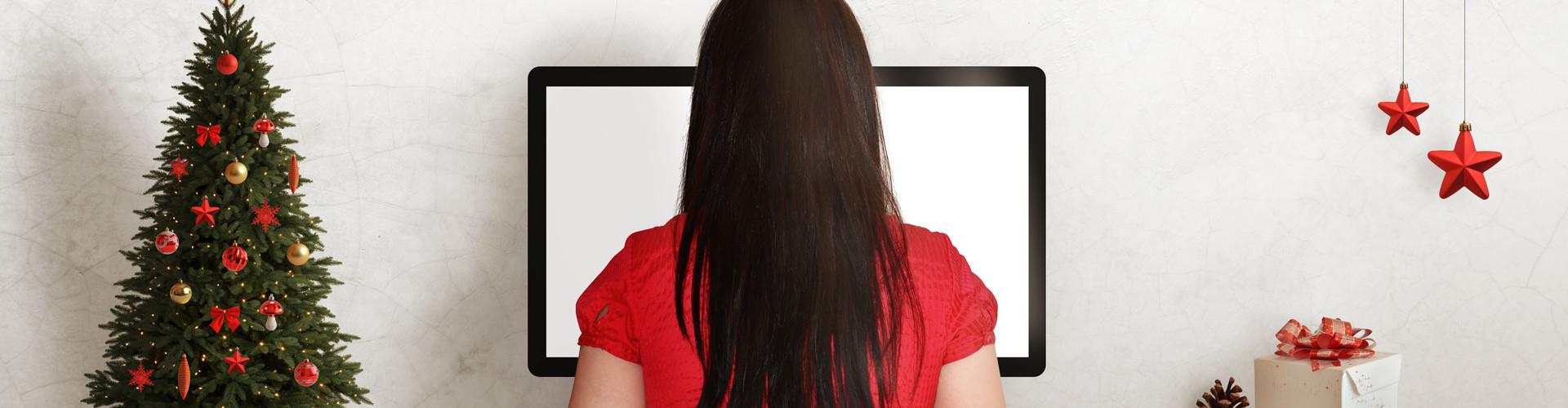 Eine Frau arbeitet am Computer. Auf dem Schreibtisch steht Weihnachtsdekoration. © Stanisic Vladimir, stock.adobe.com