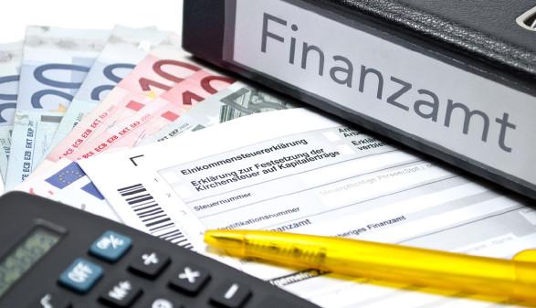 """Auf einem Tisch liegen Geld, ein Stift und ein Taschenrechner, eine Einkommensteuererklärung und ein Ordner mit der Aufschrift """"Finanzamt"""" © Stockwerk-Fotodesign, stock.adobe.com"""