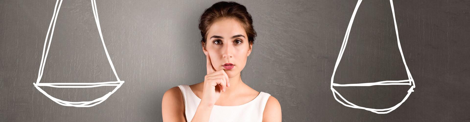 Junge Frau steht nachdenklich zwischen zwei Waagschalen, die an eine Tafel hinter ihr gemalt sind © lassedesignen, stock.adobe.com