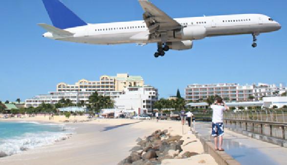 Ein Flugzeug im Landeanflug fliegt tief über einem Spaziergänger auf einer Strandpromenade. © liveostockimages, Fotolia