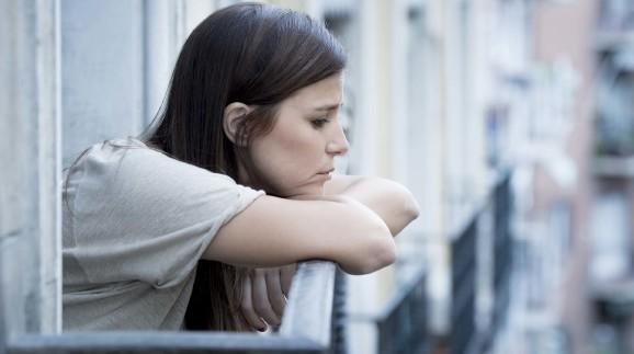 Junge Frau steht besorgt auf dem Balkon © Wordley Calvo Stock, stock.adobe.com