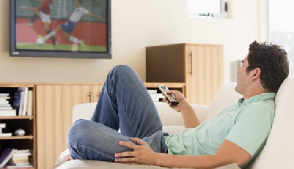 Junger Mann liegt auf der Couch und schaut Fernsehen. © Monkey Business, Fotolia