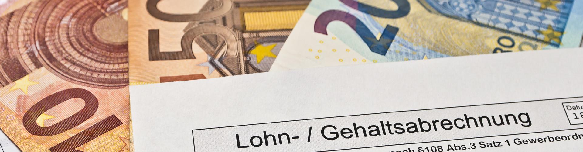 Eine Lohnabrechnung liegt auf mehreren Gelscheinen © Stockfotos-MG, stock.adobe.com